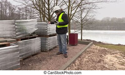Construction engineer using tablet PC and numbering near...