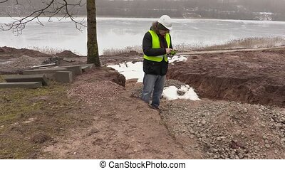 Construction engineer using tablet PC and walking near the...