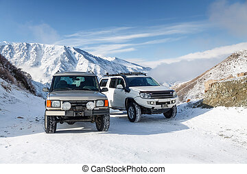 Two SUVs on a snowy mountain road - Two Sport Utility...