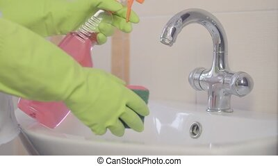 woman doing chores in bathroom at home, cleaning sink and...