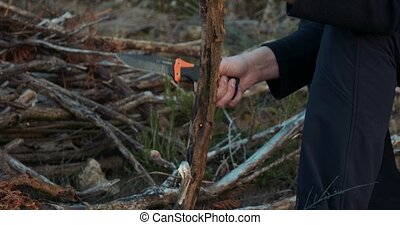 Man Batoning Branches With A Survival Knife For A Camp Fire