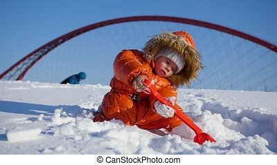 happy child playing in the Park on a Sunny winter day. Snowy...
