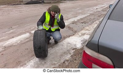 Man with tires talking on phone near car
