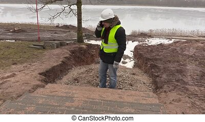 Construction engineer talking on smart phone near unfinished...