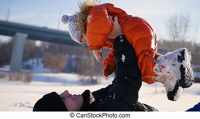 Man playing with your child in a sunny winter time. Holding in his arms. Winter landscape