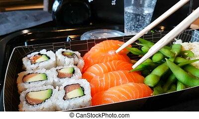 Man Eating Sushi in a Restaurant - Man Eats Sushi in...