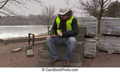 Worker sitting on paving bricks and using tablet