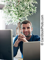 Smiling businessman sitting at a computer in an office