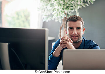 Focused businessman sitting at a computer in an office