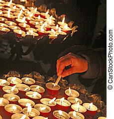 hand of an elderly woman hand lighting a candle during the...