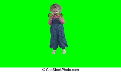 Cute little girl measure big party glasses isolated on green even background