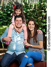 Family of tree in park - Happy hispanic family of three in...