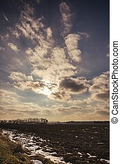 Dramatic cloudy sky over the early spring landscape with field