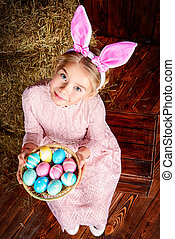 colored eggs - Easter holidays. Cute little girl in Easter...
