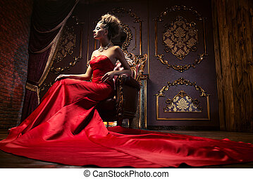 richness - Magnificent young woman in luxurious red dress...