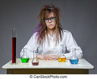 Serious shaggy scientist in lab on gray background