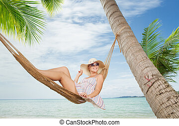 view of nice young lady swinging in hummock on tropical...