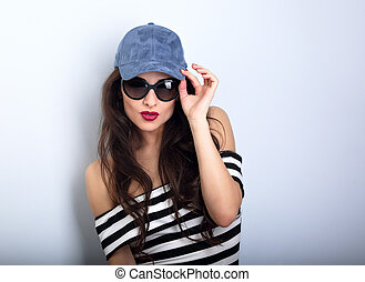 Happy sexy young woman in sunglasses and blue baseball cap posing and looking in striped blouse. Closeup portrait