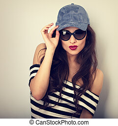 Emotional sexy young woman in sunglasses and blue baseball cap posing and looking in striped blouse. Closeup vintage toned portrait
