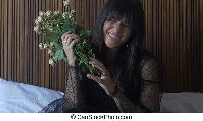 Brunette female holding bouquet of roses - Smiling brunette...