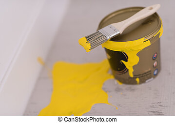 Yellow paint tin can with brush on top with yellow strokes...