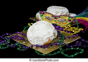 Fat Tuesday paczki with Mardi Gras party beads and mask on...