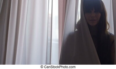 Female peeking out from behind the curtains - Smiling...