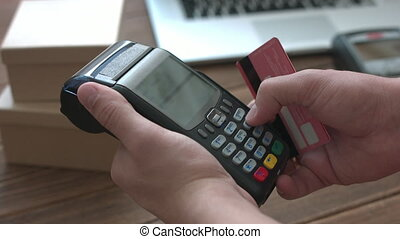 Man's hand pushing the button and swipe credit cardterminal...