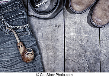 Wooden pipe for smoking on blue jeans, gray wooden...