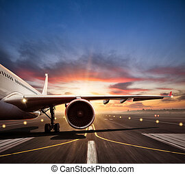 Close-up of airplane on runway in sunset light - Close-up of...