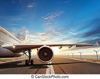 Close-up of airplane on runway in sunset light