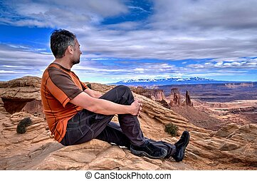 Man hipster on cliff looking at canyon views.