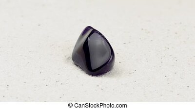 Purple amethyst rotating on white sand - Purple amethyst gem...