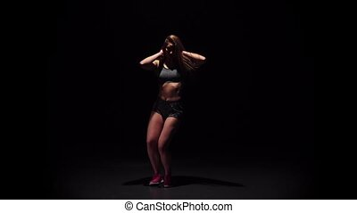 Woman dancing hip-hop movement in dark studio face to viewer
