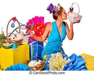 Woman in easter style holding rabbit and flowers in basket.