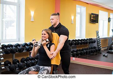 Woman with her personal fitness trainer in the gym exercising power gymnastics with a barbell
