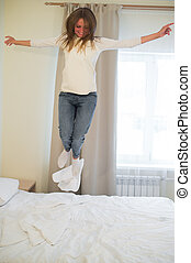 Portrait of a young happy woman jumping on the bed.