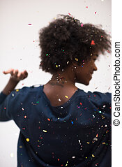 African American woman blowing confetti in the air -...