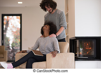 multiethnic couple hugging in front of fireplace - Young...