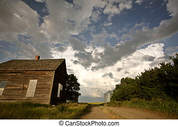 Storm clouds behind an old Saskatchewan homestead