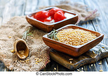 Uncooked Italian pasta orzo in a bowl. - Bowls with orzo...