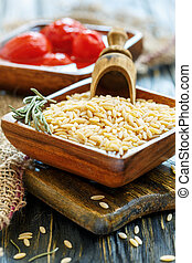 Orzo pasta and wooden scoop in bowl close-up. - Orzo pasta...