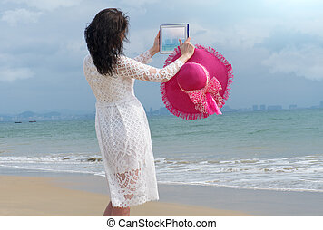 Girl with bright hat and iPad makes the photo