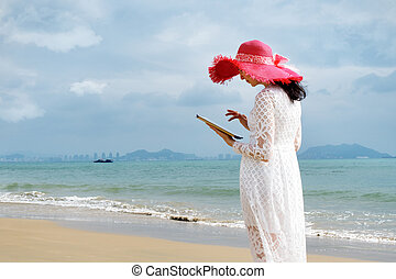 Girl in hat on the beach with her ipad