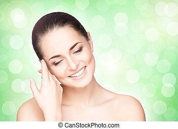 Portrait of young, beautiful and healthy woman over green blurry background. Healthcare, spa, makeup and face lifting concept.