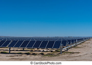 Many solar panels in the desert with blue sky - Many wind...