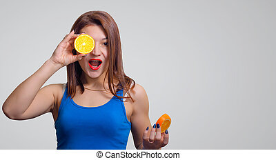 Cheerful young girl with an open mouth and a slice of orange