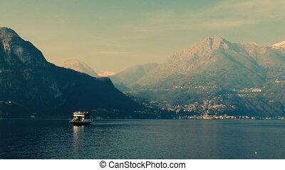 Boats sailing through a mountain lake. Lake Como, Italy.