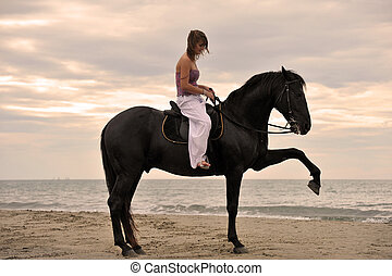 girl and horse on the beach - beautiful black stallion on...