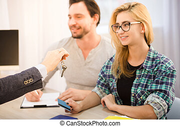 Manager giving key to couple - Toned of young businessman...